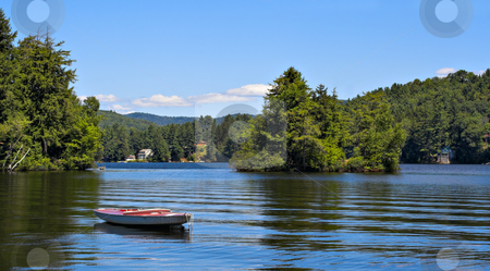 Mountain Lake stock photo, A lake in the mountains with a small boat in the foreground. by Stephen Bonk