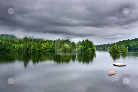 Stormy Lake Scene stock photo, A lake during a rain storm. There are dark, ominous rain clouds overhead by Stephen Bonk