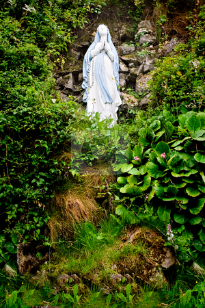 Virgin Mary Statue stock photo, A statue of Virgin Mary on a hill surrounded by foliage by Stephen Bonk