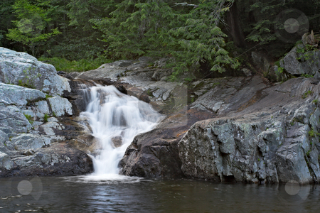 Buttermilk Falls stock photo, A waterfall surrounded by rocks and trees. by Stephen Bonk