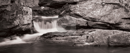Waterfall Panorama in B&W stock photo, A small waterfall over rock in panorama format. Photo is in black and white. by Stephen Bonk