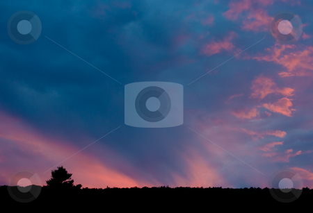Sunset and Mountain Tree stock photo, A colorful evening sunset. The top of a mountain and an isolated tree can be seen at the bottom of the frame with the colorful sky above. by Stephen Bonk