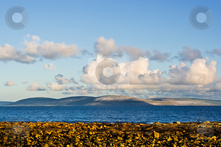 Galway Bay and Burren stock photo, Galway Bay in Ireland from the town of Spiddal with The Burren across the bay. Photo is layered from front to back with Rocks, Galway Bay, The Burren, and sky. by Stephen Bonk