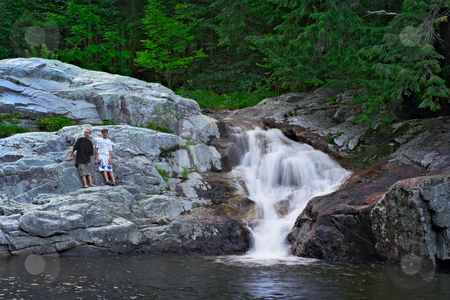Buttermilk Falls and Kids stock photo, A waterfall with two boys standing on surrounding rocks by Stephen Bonk