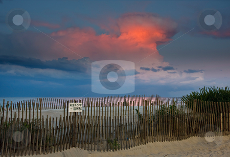 Beach Sunset and Thunderhead stock photo, An evening scene at the beach. The last rays of light are dramatically lighting the clouds in the sky of a nearby thunderstorm. by Stephen Bonk