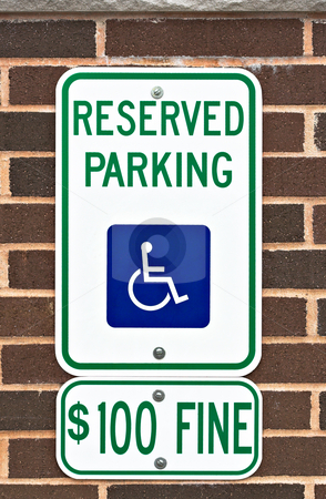Reserved Parking Sign stock photo, A reserved parking sign on a brick wall. There is a picture or symbol of a wheelchair on the sign along with a message for a one hundred dollar fine. by Stephen Bonk