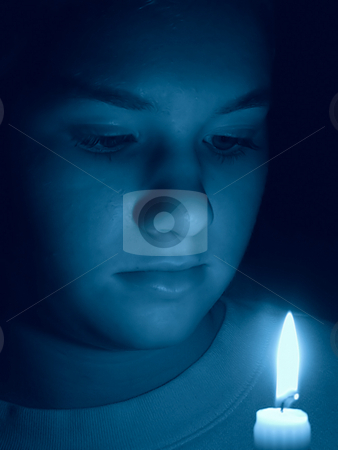 Young Girl Portrait by Candlelight - Birthday Wish stock photo, Portrait of a young girl lit only by a single candle. She is gazing at the candle making a birtday wish. Photo has a blue tone. by Stephen Bonk