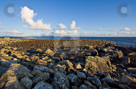 Galway Bay stock photo, Galway Bay with a large rock jetty in the foreground. The Burren can be seen in the background with cumulus clouds against a blue sky. by Stephen Bonk
