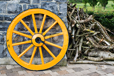 Wooden Wagon Wheel and Branches stock photo, An old antique yellow wooden wagon wheel leaning against a stone wall. There is a pile of tree branches laying next to it. by Stephen Bonk