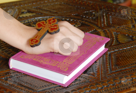 Religious life stock photo, Hand on red Bible with wooden cross by Julija Sapic