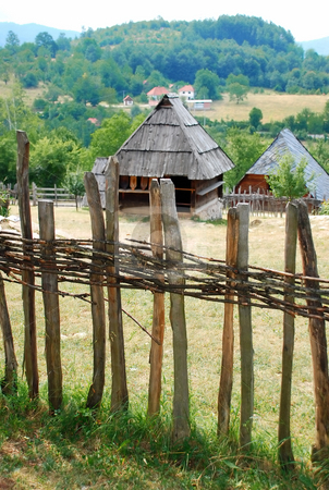 Rural landscape Serbia stock photo, Ethnic Serbia, wooden house behind fence over rural landscape by Julija Sapic