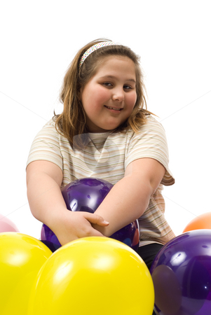 Balloons stock photo, A young girl sitting with a pile of colored balloons, isolated against a white background by Richard Nelson