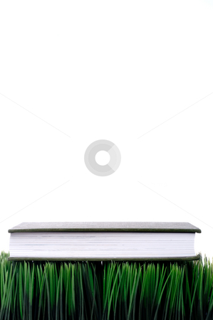 Green hardcover book sitting on grass with a white background wi stock photo, Green hardcover book sitting on grass with a white background with space for copy by Vince Clements