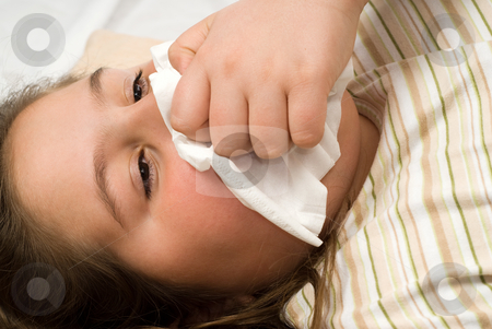 Blowing Nose stock photo, Closeup view of a young girl blowing her nose with a tissue by Richard Nelson