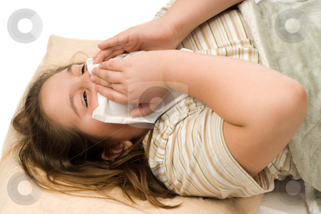 Sick Kid stock photo, A sick child blowing her nose while lying in bed, isolated against a white background by Richard Nelson