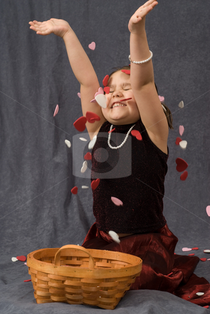Child Throwing Confetti stock photo, A young girl sitting on the floor and throwing heart shaped confetti into the air by Richard Nelson