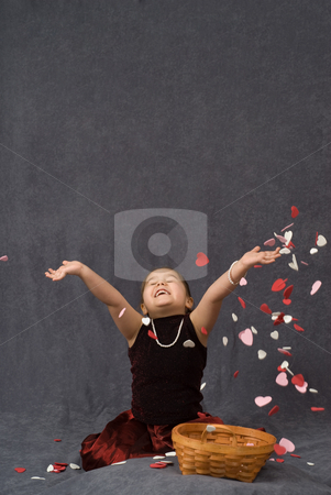 Child Throwing Confetti stock photo, A young girl throwing heart shaped confetti with copy-space above her by Richard Nelson