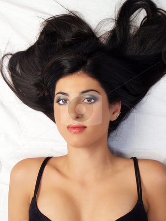 Young middle eastern woman on floor portrait stock photo, Young middle eastern woman in black bra by Jeff Cleveland