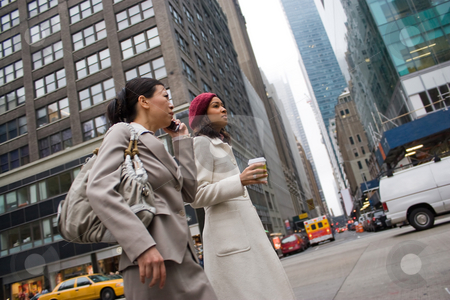 City Business Women stock photo, Two business women walking in the big city. One woman is on her cell phone.  Slightly shallow depth of field. by Todd Arena