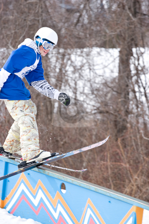 Grinding the Rail stock photo, A young man performs a rail slide on skis. by Todd Arena