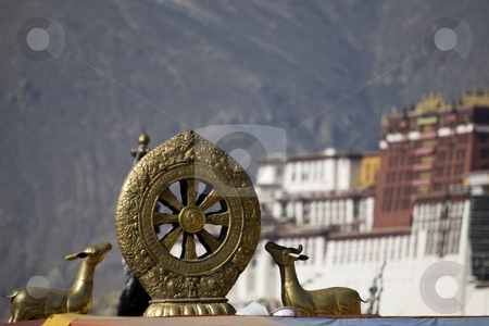 Wheel of life stock photo, Tibetan golden statue with Potala Palace and mountains in the background by Marius Blajut