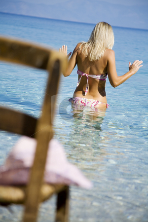 Going in the sea stock photo, Blond female slowlyentering the water at the beach by Liv Friis-Larsen