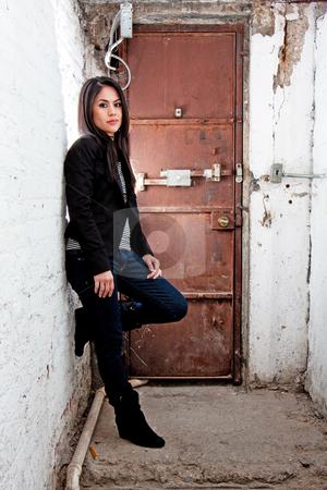Girl in front of door stock photo, Beautiful Caucasian girl standing in basement in front of brown door leaning against white walls by Paul Hakimata