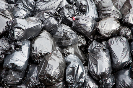 Garbage bags stock photo, A pile of black garbage bags with tons of trash by Paul Hakimata