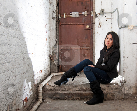 Girl sitting in basement stock photo, Beautiful Caucasian girl sitting on concrete floor in basement in front of brown door by Paul Hakimata