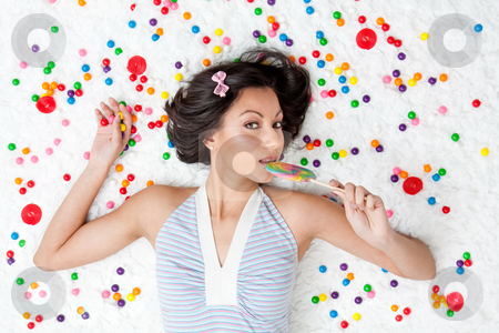 Lollipop girl stock photo, Young Latina woman laying on ruffled cloud like floor between colorful bubblegum balls eating a lollipop by Paul Hakimata