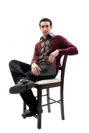 Handsome guy sitting on chair stock photo, Handsome guy wearing business casual clothes sitting on a high chair with legs crossed and arm resting, isolated by Paul Hakimata