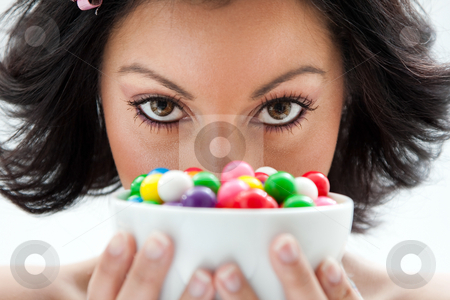Candy girl stock photo, Beautiful candy girl closeup holding a bowl of colorful bubblegum candy balls in front of her face by Paul Hakimata