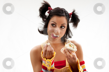 Cupcake girl stock photo, Beautiful Latina girl eating a cupcake with her fingers and licking her icing covered lip, isolated by Paul Hakimata