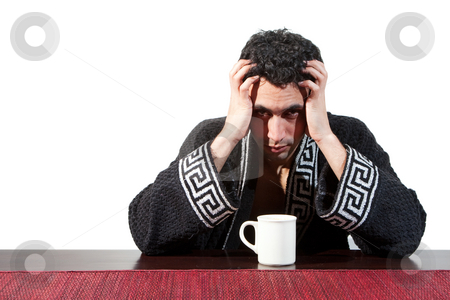 Morning guy drinking coffee stock photo, Handsome guy in the morning who just woke up sitting at a table in his robe and hands in his hair with a cup, isolated on white by Paul Hakimata