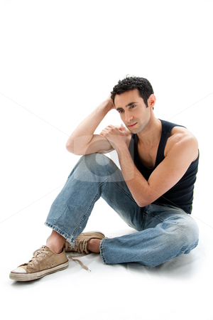 Handsome guy sitting on floor stock photo, Handsome Caucasian guy wearing black tank top and jeans sitting on floor thinking, isolated by Paul Hakimata