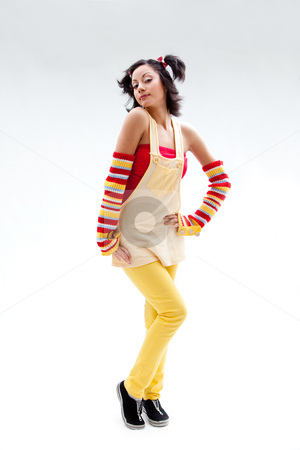 Fun girl standing stock photo, Beautiful fun latina girl with bright colored arm warmers and ponytails with red ribbons in her hair standing, isolated by Paul Hakimata