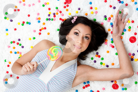 Lollipop girl stock photo, Young Latina woman laying on ruffled cloud like floor between colorful bubblegum balls holding a lollipop by Paul Hakimata