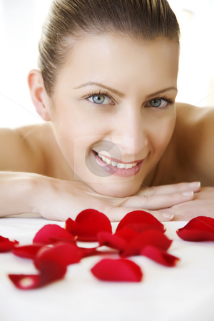 Pampering stock photo, Smiling young femalebehind sprinkled rose-petals by Liv Friis-Larsen