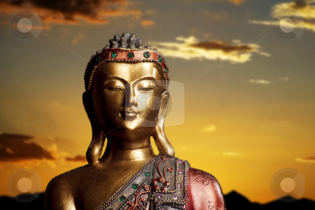Buddha Statue at Sunset stock photo, Golden Buddha statue against a bright orange sky by Scott Griessel