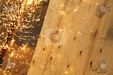 Sparks from a grinder landing on a wooden panel stock photo, Sparks from a grinder landing on a wooden panel by Chris Alleaume