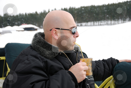 Relaxing Coffee in Winter stock photo, Handsome man wearing sunglasses relaxing and having coffee on a winter day. by Denis Radovanovic