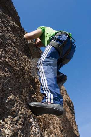 Man Rock Climbing stock photo, Athletic young man climbing on the face of a rock wall. Shot is taken from below looking up by Orange Line Media
