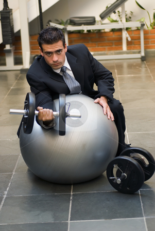 Man Lifting Weights - Weights Lowered stock photo, Attractive young executive doing biceps curls in a gym, dressed in a business suit. by Orange Line Media