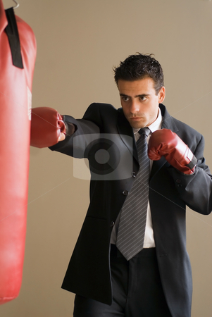 Competitive Businessman stock photo, Businessman wearing boxing gloves punching a heavy bag. Isolated. by Orange Line Media