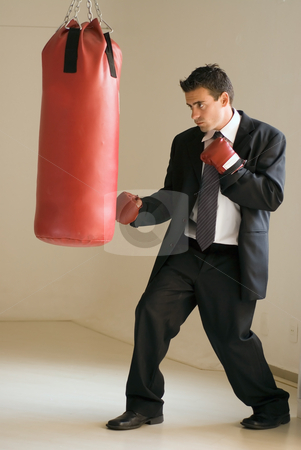 Businessman and Boxer stock photo, Young attractive businessman throwing a punch at a heavy punching bag by Orange Line Media