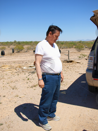 Retiree Standing in Desert stock photo, A shot of a older man standing in the desert in a white t-shirt. by Orange Line Media
