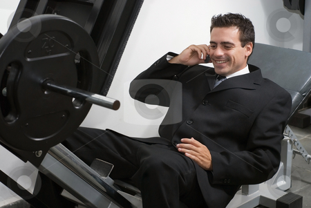 Taking a Call in the Gym stock photo, Businessman on leg press machine taking a call. by Orange Line Media