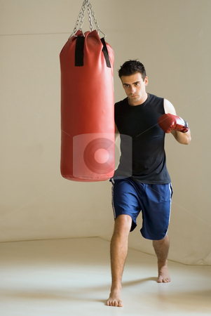 Man with Punching Bag stock photo, Fit, attractive man about to punch a heavy bag. He is wearing boxing gloves and the shot is isolated against a white background. by Orange Line Media