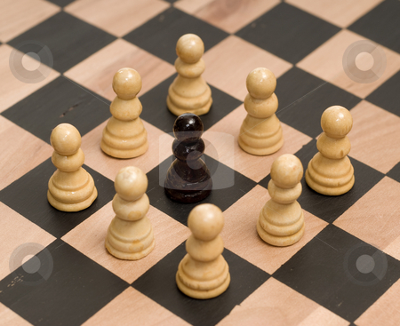 Racism stock photo, Concept image of racism, with white chess pieces surrounding a black one by Richard Nelson