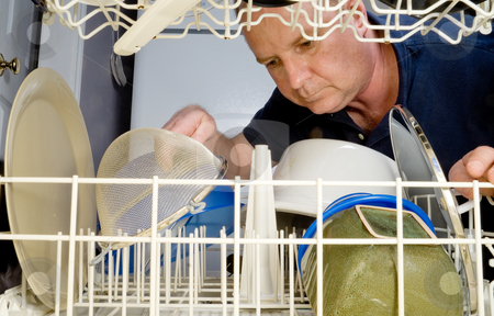 Dishwasher stock photo, A man loading or unloading a dishwasher. by Robert Byron